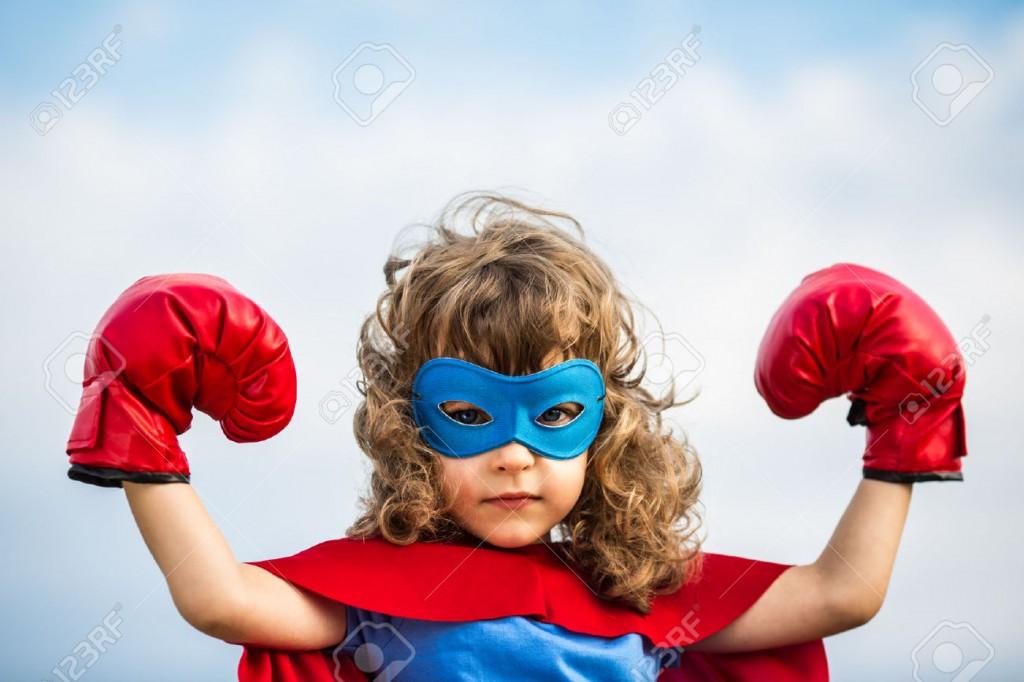 22437205-Superhero-kid-wearing-boxing-gloves-against-blue-sky--Stock-Photo
